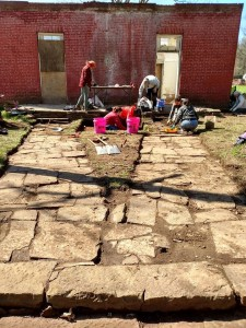 : Crew cleaning the stone walkways at the Methodist Manse at Cane Hill during the 2015 Spring Break Dig.
