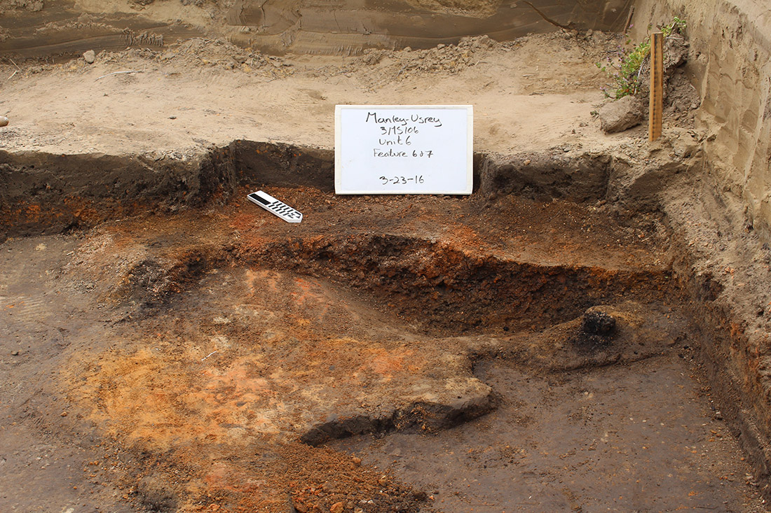 Figure 3: The hearth has been bisected and half of the fill removed.  Part of the floor was also burned and solid (orange area extending away from the bowl-like hearth).  An in situ wooden post was also found next to the hearth (black spot on the right near the edge of the hearth).