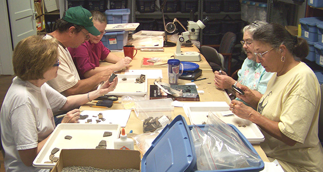 Florence Davis, Tony Caver, Vanessa Hanvey, Mary Ann Goodman, and Judy Thye analyze artifacts from 3HS60 (Hedges) in the HSU Research Station Archeology Lab in 2011.