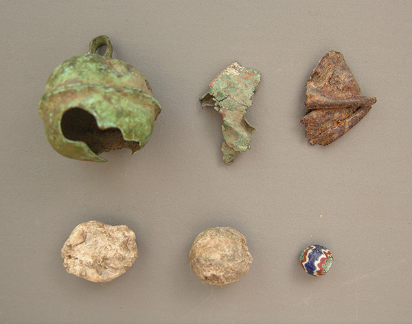 Early sixteenth-century Spanish artifacts from the Parkin site. Top (l to r): Clarksdale bell of brass; Clarksdale bell fragment of brass; possible Clarksdale bell fragment of bronze. Bottom (l to r): lead shot that was fired or damaged; unfired lead shot (.61 caliber); seven-layer faceted chevron bead. ARAS photo.