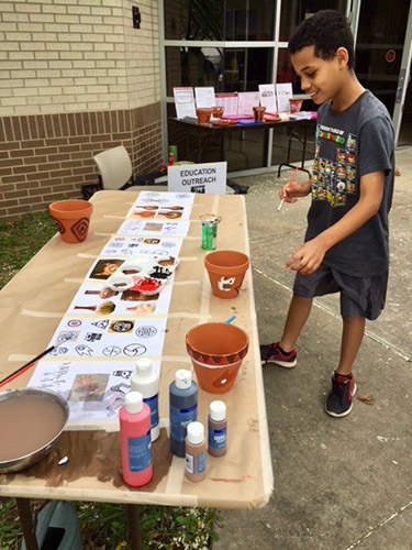 A participant at the Arkansas Archeological Survey's UA Fayetteville Research Station paints pottery that will be used as education outreach tools .