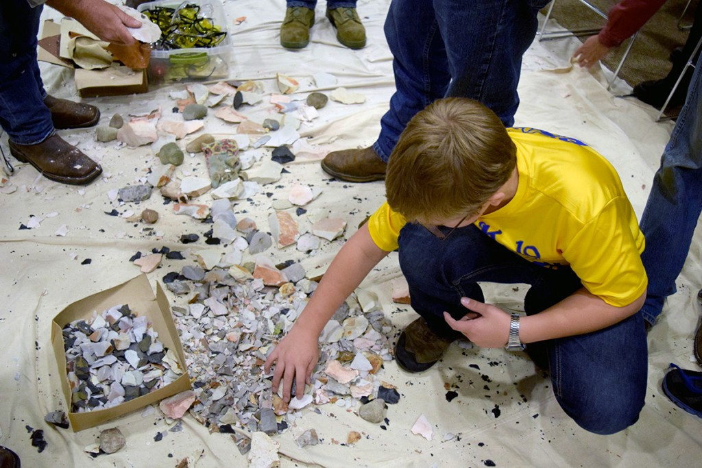 A Cub Scout from Pack 19 learns about flint knapping.
