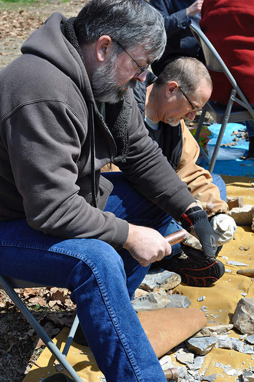 Society member Paul Knapp tries his had at flint knapping.