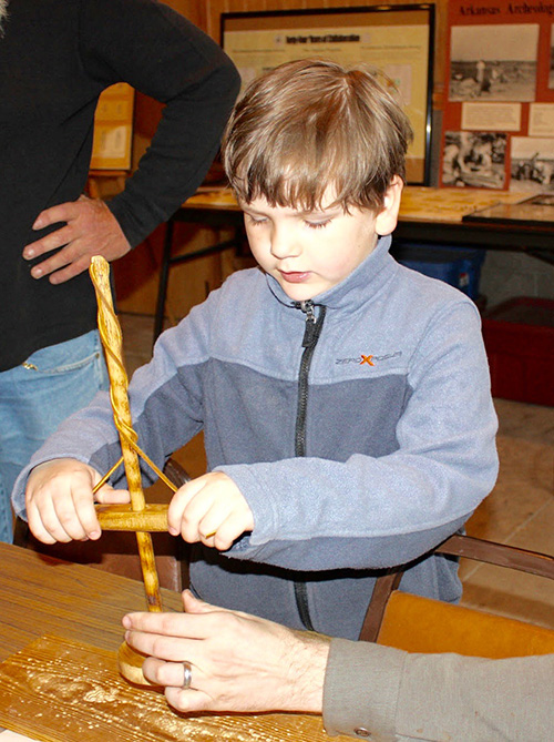 A local student tries his hand at using a replica drill
