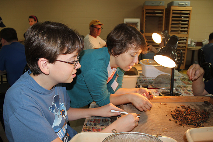 Dr. Emily Beahm helps a young volunteer sort through artifacts.