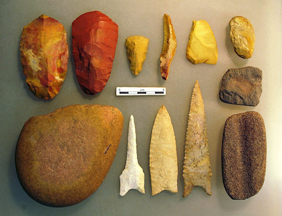 Dalton Tool Kit, clockwise from top left corner: two adzes, an end scraper, a backed knife, a flake cutting tool, a chert hammer, a sandstone abrader, a grooved sandstone abrader, a heavily resharpened Dalton point, a minimally resharpened Dalton point, a Dalton perforated, and an Edge abraded cobble.