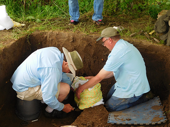 ARAS-Parkin station archeologist Jeffrey M. Mitchem and ARAS-UAFS station archeologist Timothy S. Mulvihill removing the possible cross base after wrapping it for protection. Photo courtesy of Jessica Fleming Crawford, The Archaeological Conservancy.