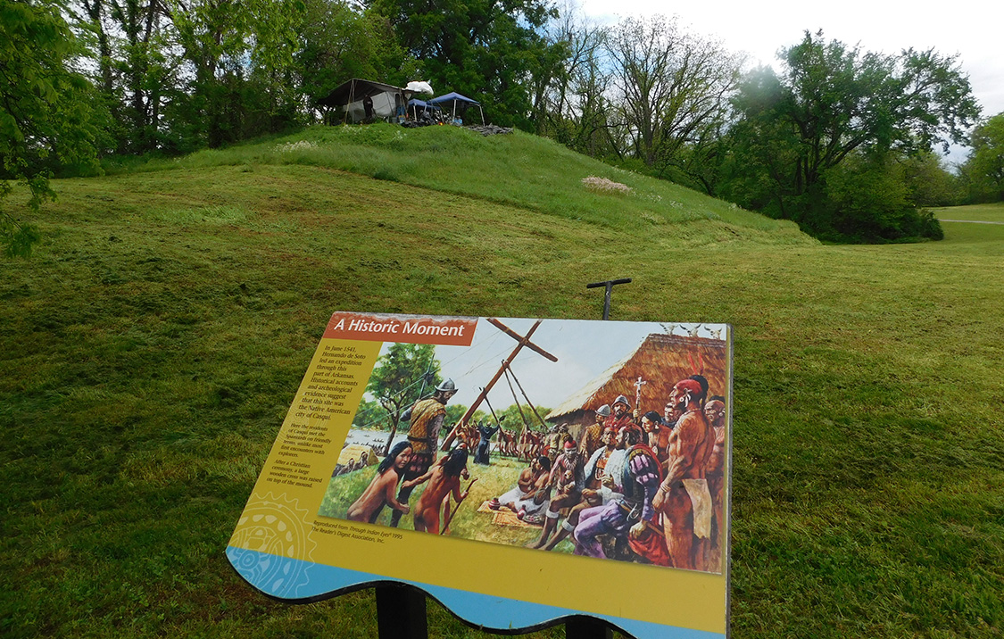 Interpretive sign depicting the raising of the cross at Casqui with the possible cross excavations ongoing in the background at Parkin Archeological State Park. Photo courtesy of Jessica Fleming Crawford, The Archaeological Conservancy.