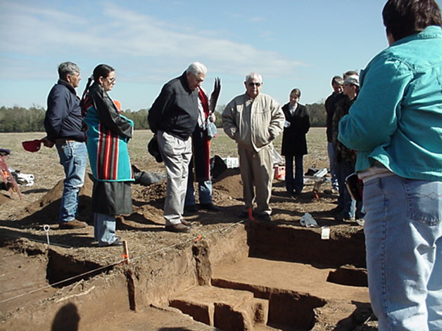 John Berry (behind Jess McKibben) holding eagle feather fan and giving a cedar smoke blessing to archeologists and Quapaws at Wallace Bottom, November 2003.