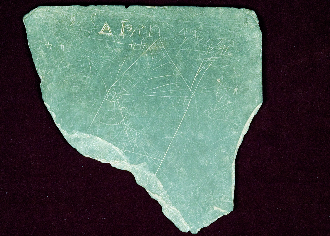 "A writing slate fragment found in the Sanders House backyard during the 1981 excavations at Historic Washington Arkansas State Park. This slate is of particular interest because a picture of a house, the number ""44"" in three different locations, and the name ""Sarah"" have been permanently scratched into its surface."