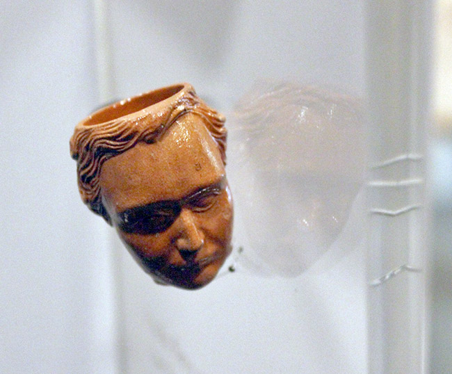 Figure 2. View of Franklin Pierce anthropomorphic pipe from the front. The pipe is made from fired red clay with a clear lead glaze (Courtesy Erik Ditzler, Arkansas Post).