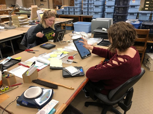 Madelyn Rose and Michelle Rathgaber log artifact collections into a new tablet-based artifact cataloging system developed by the Arkansas Archeological Survey.
