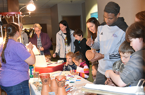 Mel Zabecki provides hands on activities including painting pottery during the Celebrate Archeology Day event. Photo by Rachel Tebbetts.