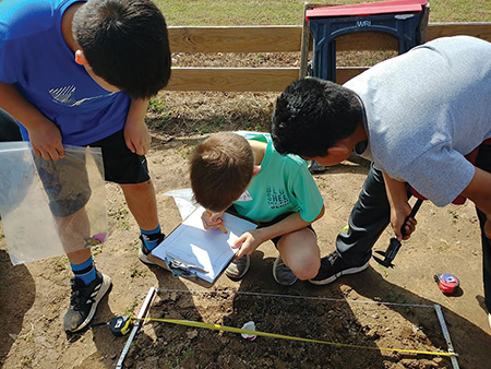 Project Dig kids develop spatial and observational skills by learning how to map artifacts in a grid and record data.