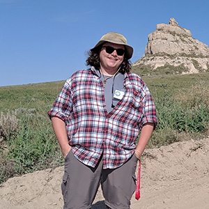 Photo of SAU station assistant Taylor Green standing in front of a rock formation in Nebraska